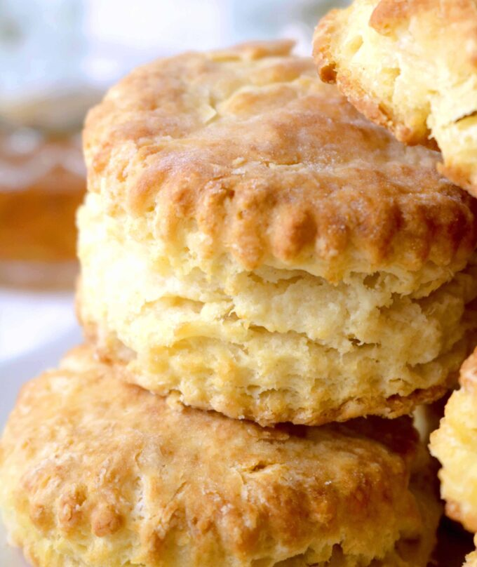 A close up shot of homemade southern biscuits stacked on top of each other.