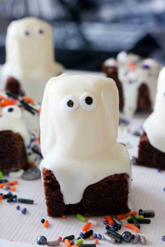 A close up shot of a square brownie with a marshmallow covered in white chocolate sitting on top to make it look like a ghost.
