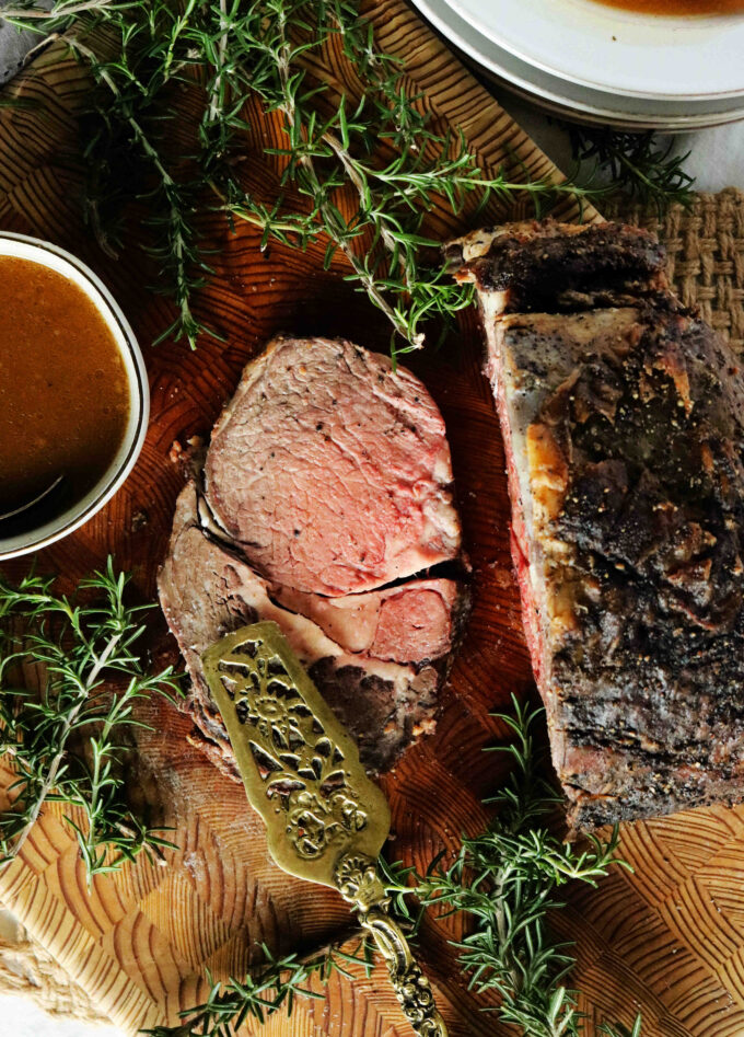 A slice of boneless prime rib cooked to a perfect medium with au jus sauce off to the side.