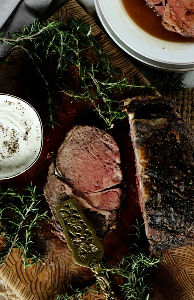 An overhead shot of beef tenderloin on a wood cutting board surrounded by fresh rosemary and a bowl of horseradish sauce.