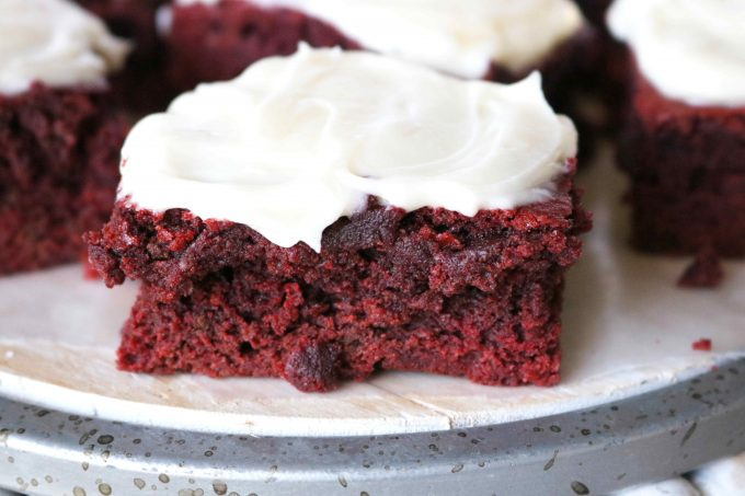 A close up of a red velvet brownie with cream cheese frosting.