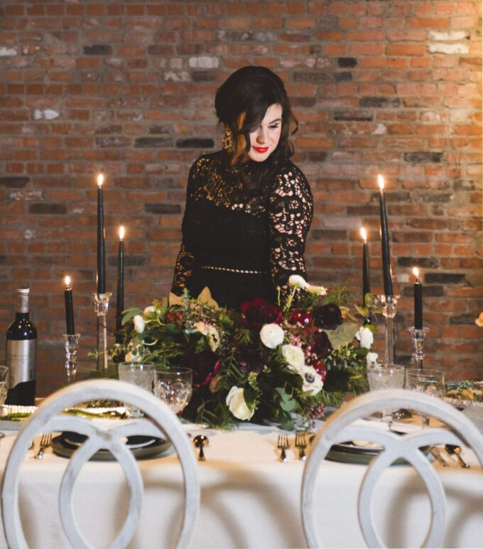A picture of Kelly Anthony standing behind a table that has a floral arrangements, black candlesticks, and place settings.