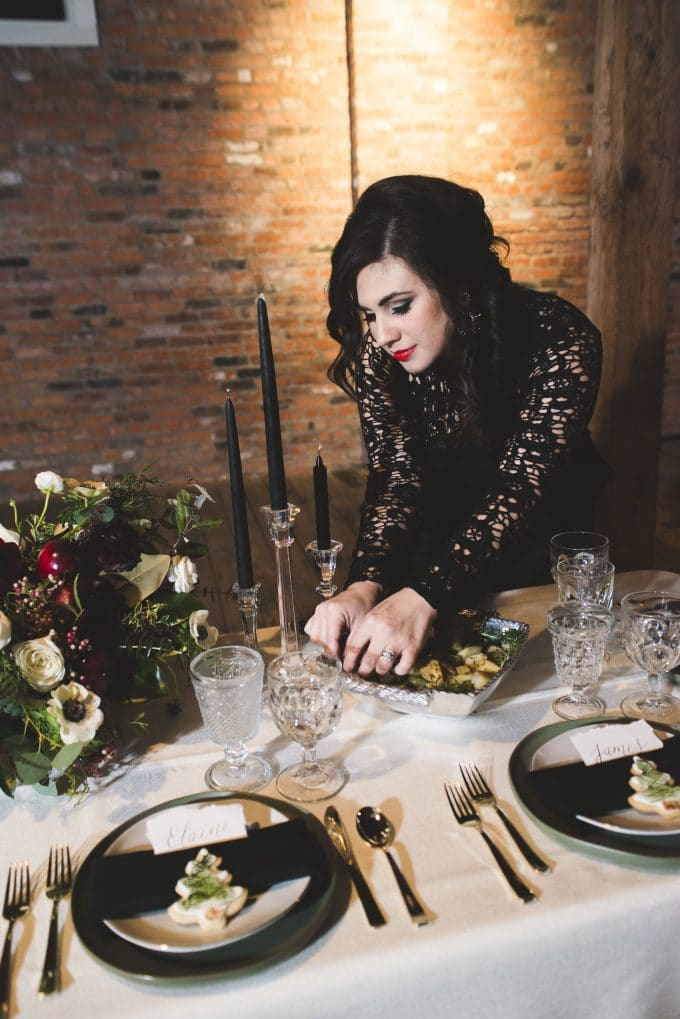 A picture of Kelly Anthony standing behind a decorated table arranging food on a serving dish.