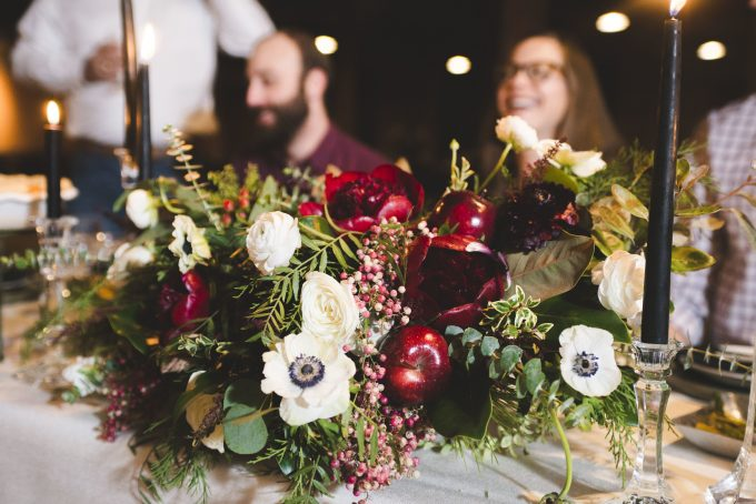 A close up shot of the floral arrangement on the table.  In the background are people sitting at the table.