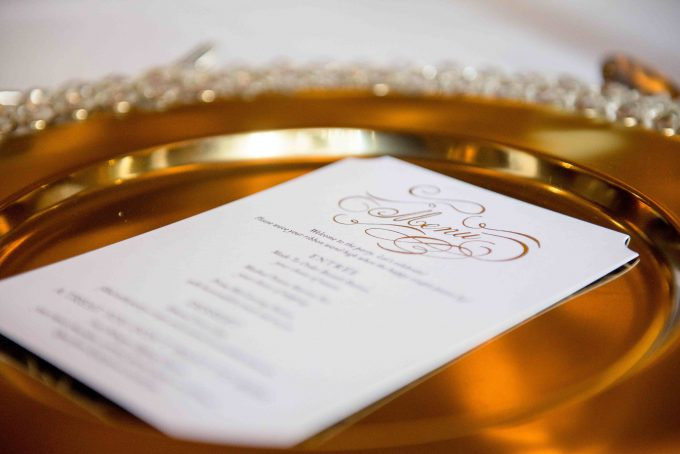A Christmas party menu lying flat on a gold plate.