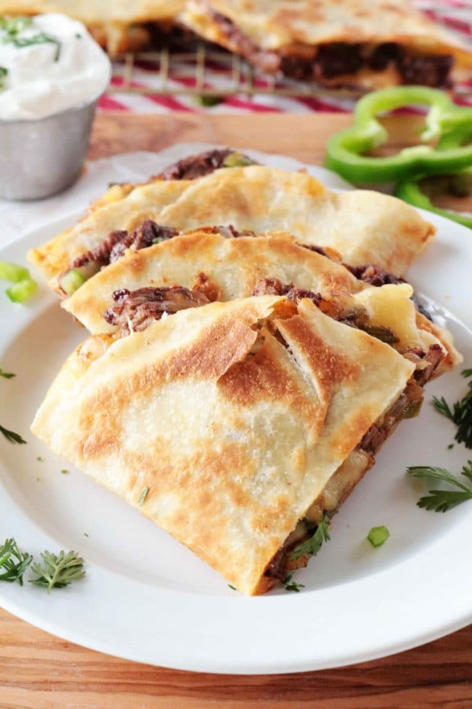 An overhead shot of layered wedges of Steak Quesadillas plated on a white plate.