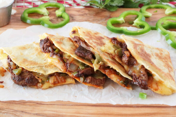 Four wedges of Steak Quesadillas layered on top of each other.  In the background of green bell pepper rounds.