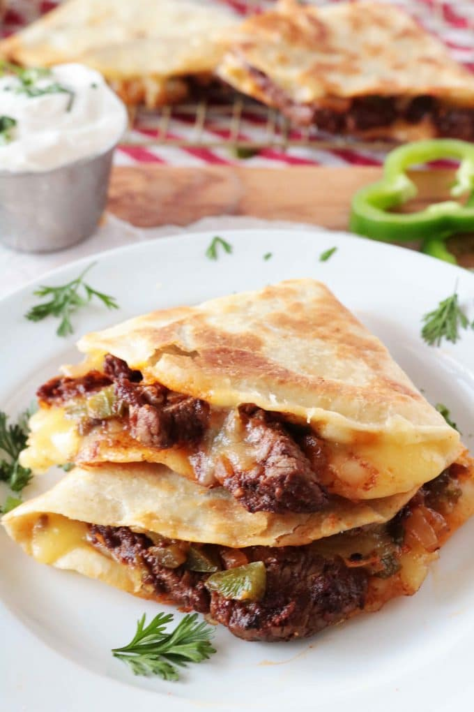 Two Steak Quesadillas wedges stacked on top of each other served on a white plate.