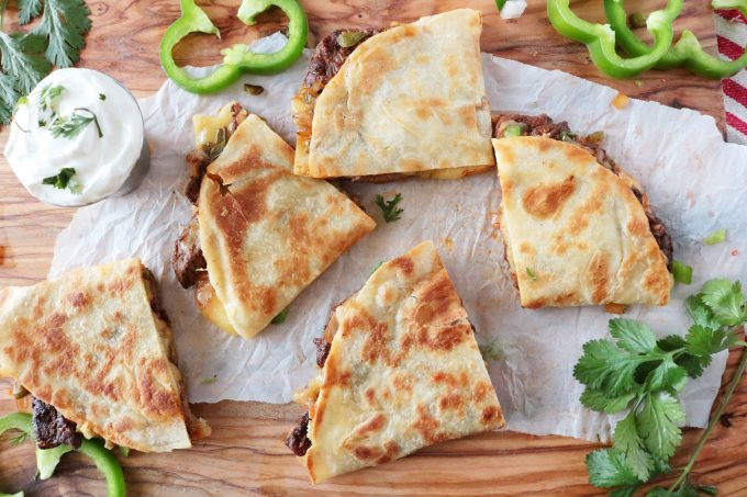 An overhead shot of Steak Quesadillas on a wood cutting board with a small bowl of Sour Cream and green bell pepper rounds.