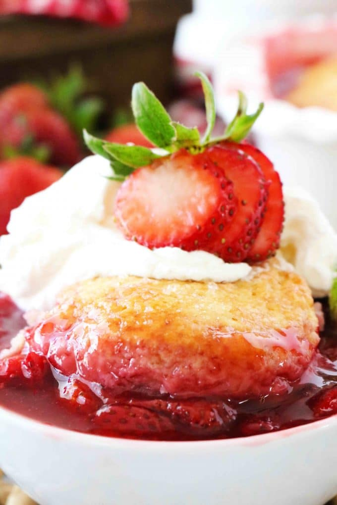 A close up shot of Strawberry Cobbler that is served in a white bowl topped with whipped cream and a fresh strawberry.