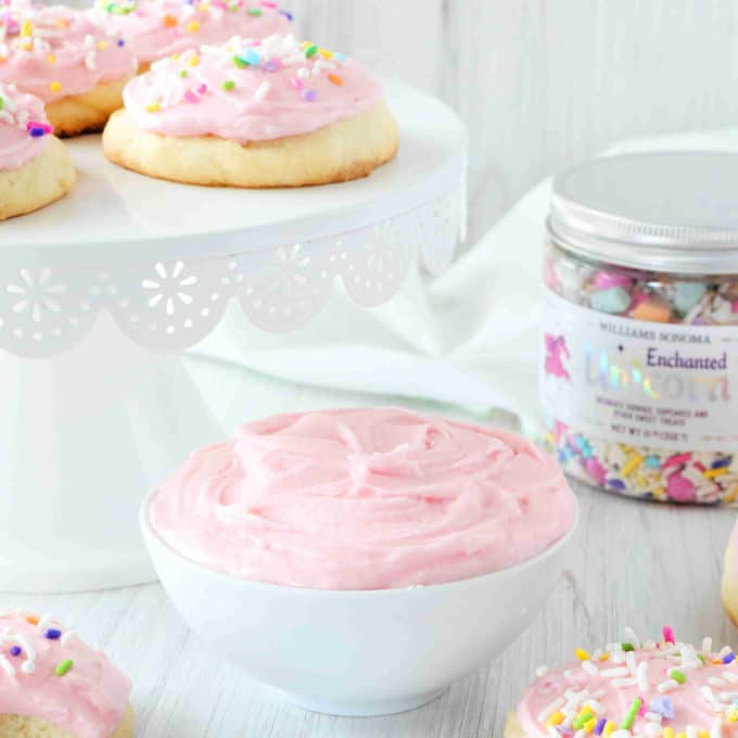 A bowl of Sugar Cookie Frosting in the center with Lofthouse cookies on a cake stand in the background.