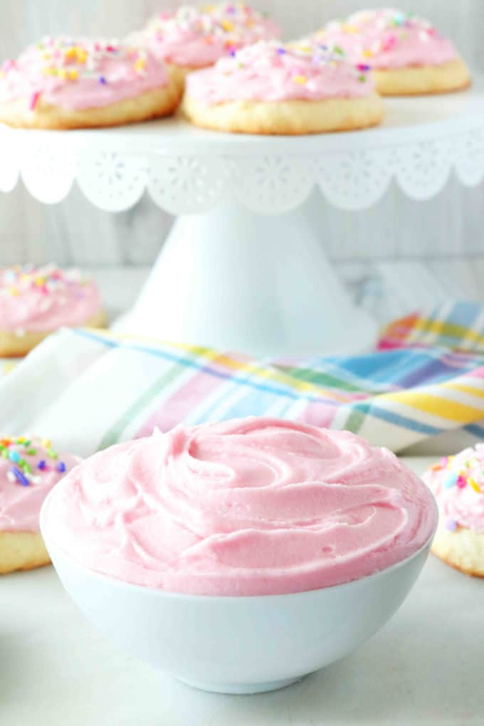A bowl of pink Sugar Cookie Frosting with a cake stand of iced sugar cookies in the background.