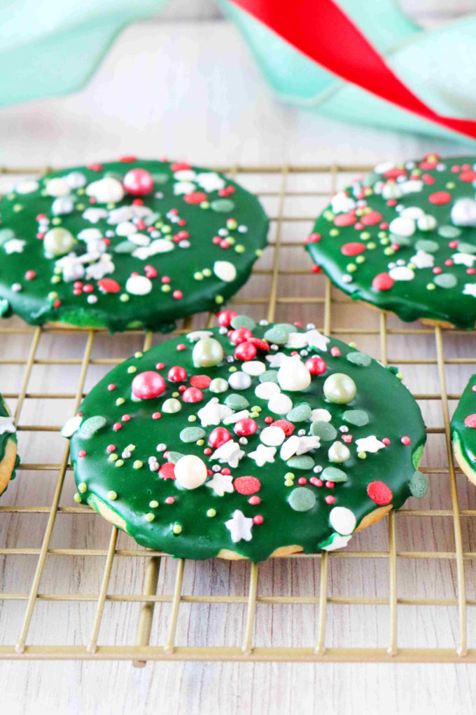 Sugar cookies iced and topped with sprinkles on a cooling rack.