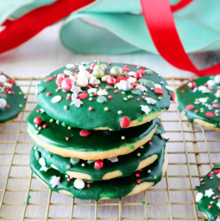 A stack of iced sugar cookies on a cooling rack with ribbon in the background.