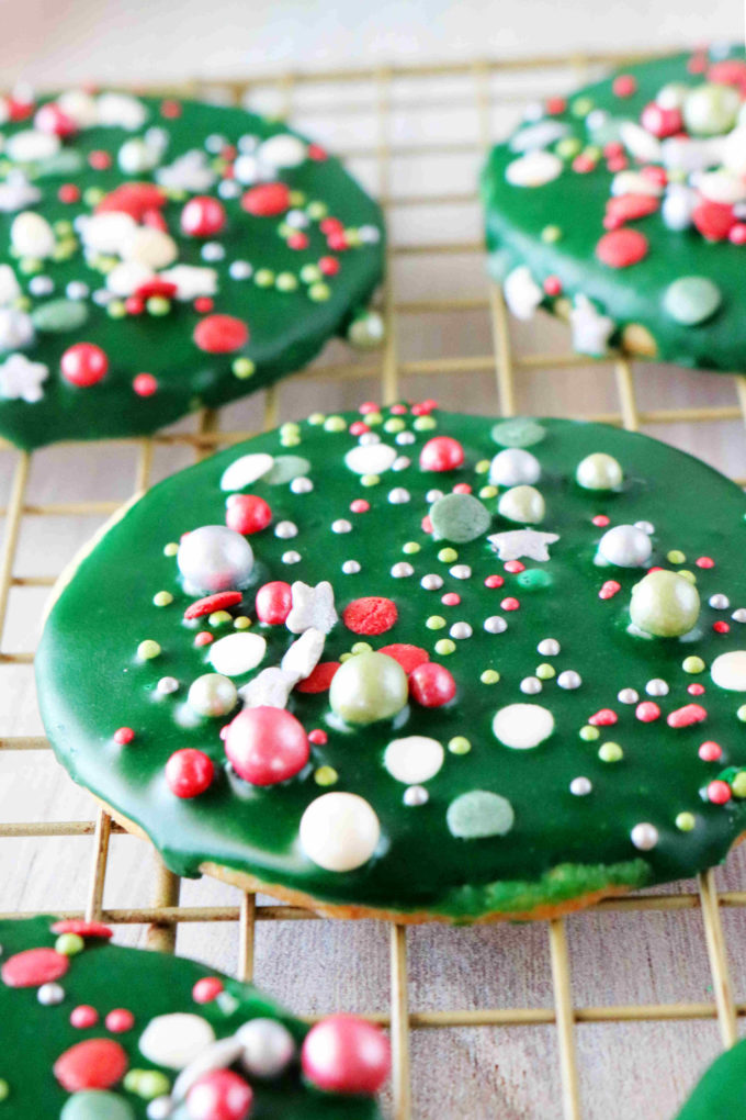 A close up shot of iced sugar cookies with green icing and sprinkles.