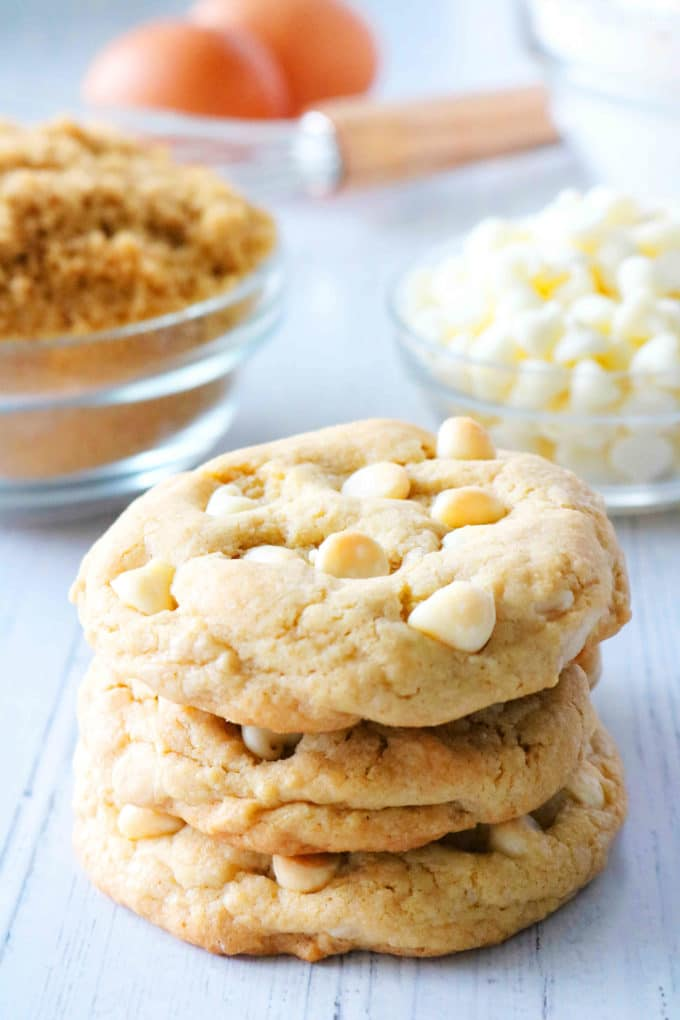 A stack of cookies with brown sugar and white chocolate chips in the background.