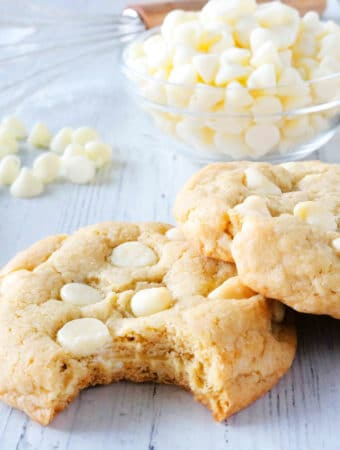 White Chocolate Chip Cookies stacked on one another with a bite taken out of one.