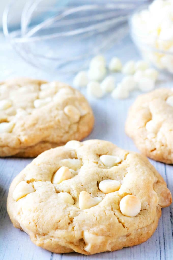 White Chocolate Chip Cookie with chocolate chips and a whisk in the background.