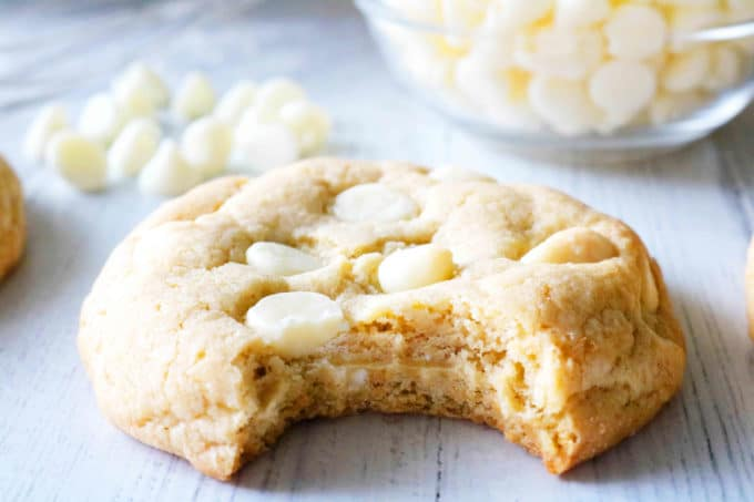 Close up of a white chocolate chip cookie with a big bite taken out of the center.