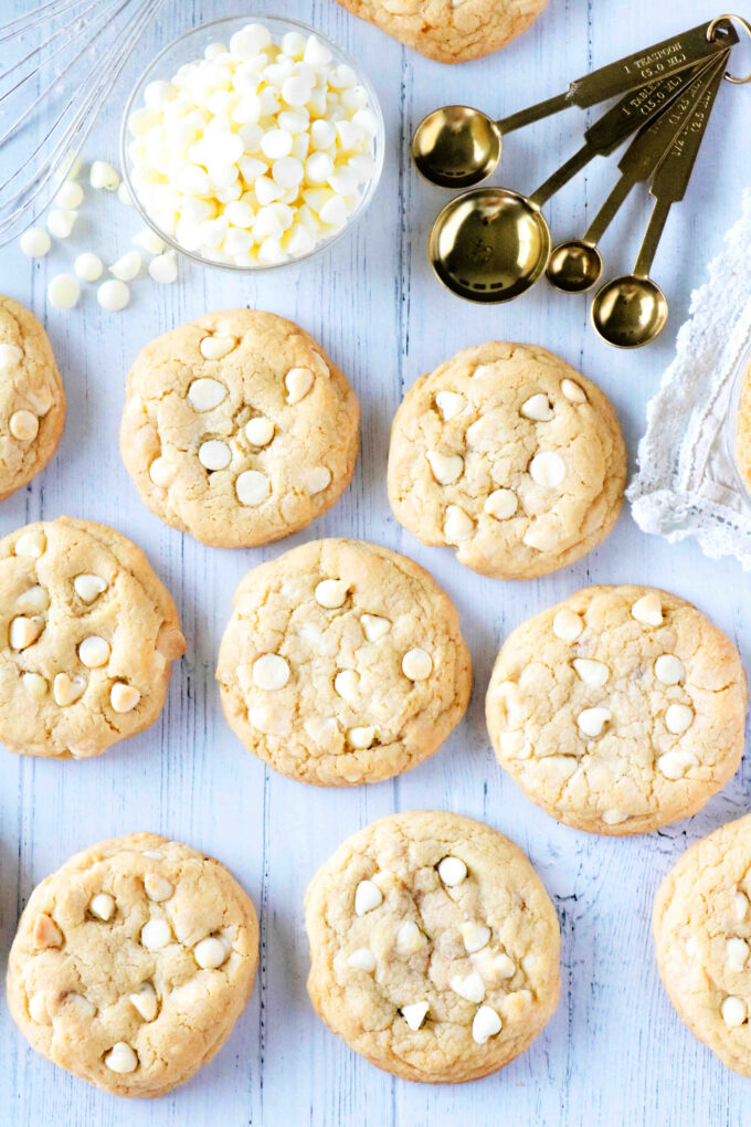 Overhead shot of cookies with teaspoons and white chocolate chips off to the side.