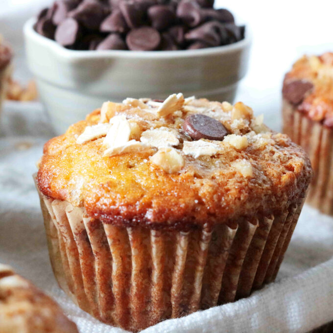 A closeup shot of Banana Oatmeal Muffins with a bowl of chocolate chips in the background.