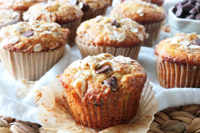 Banana Oatmeal Muffins with the wrapper peeled off and lots of muffins behind it.