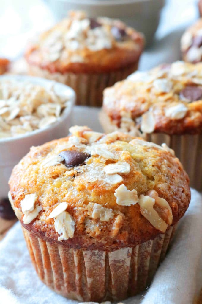 Banana Oatmeal Muffins with oats sprinkled across the top and a bowl of oats in the background.