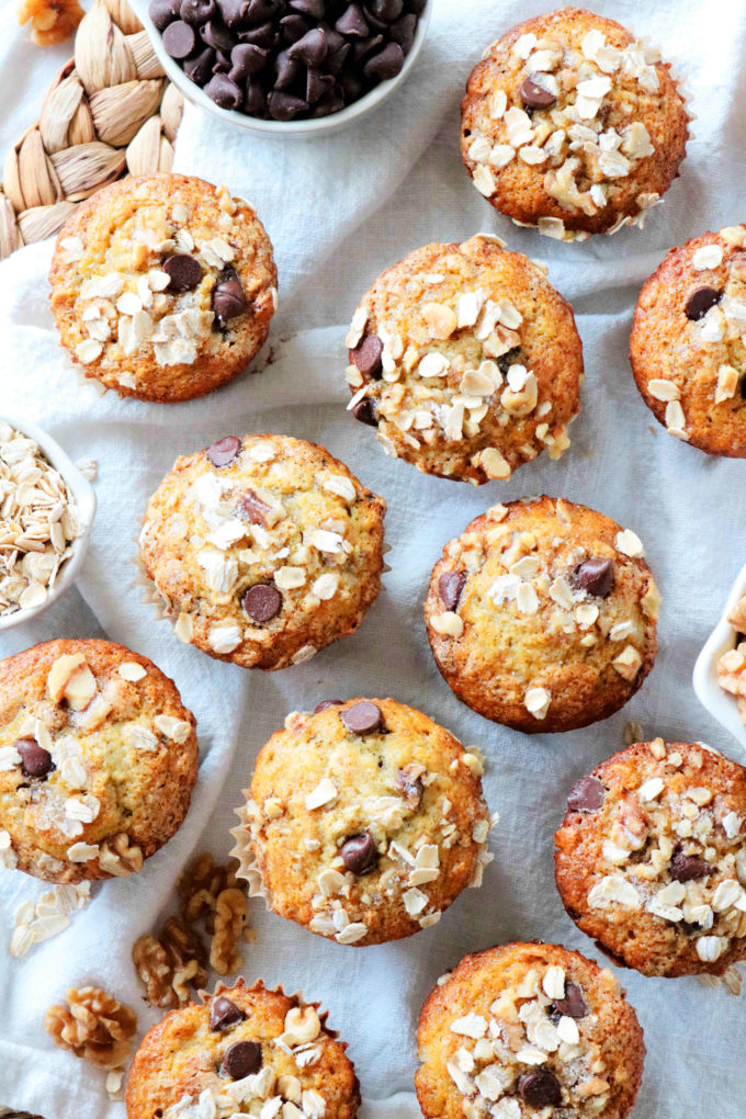 An overhead shot of muffins with oats, walnuts, and chocolate chips off to the side.
