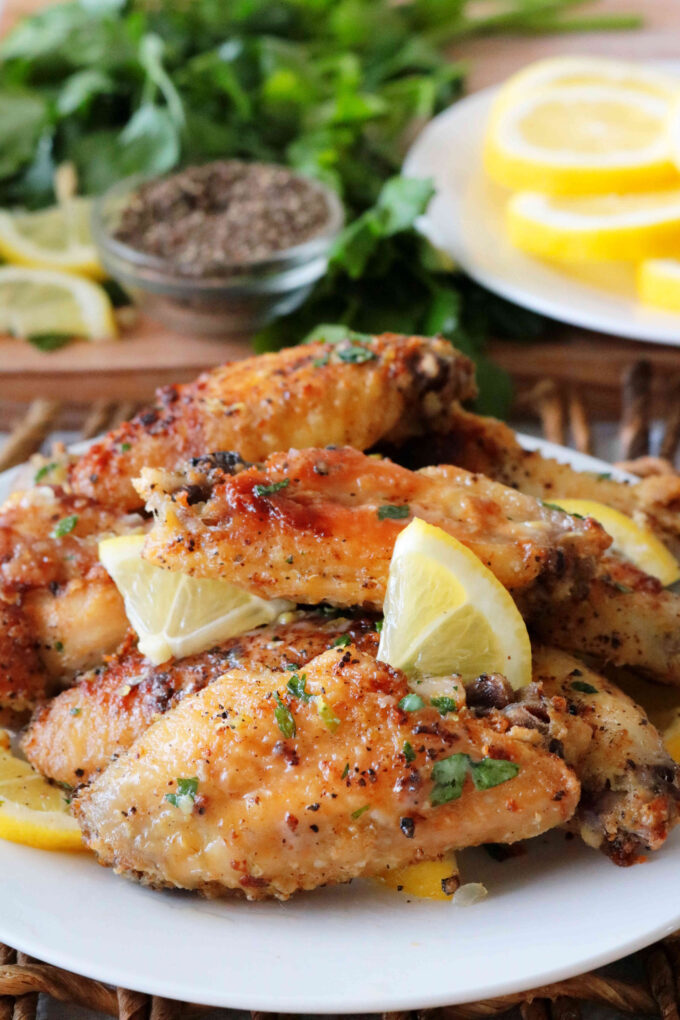 Buttery lemon pepper wings stacked on a plate.