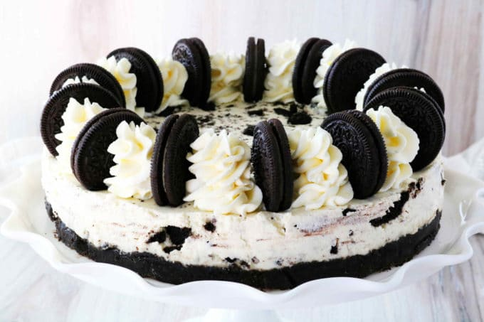 Oreo cheesecake on a cake platter with Oreos and and whipped cream decoratively arranged across the top.