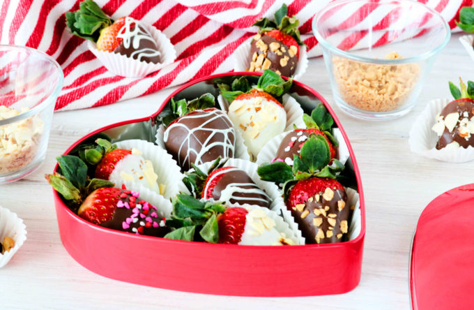 Chocolate-covered strawberries in a heart-shaped tin.