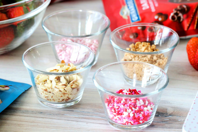 Bowls of sprinkles, nuts, and candy surrounded by strawberries and chocolate melting wafers.