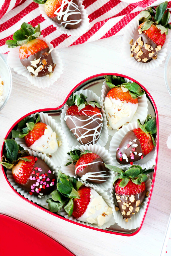An overhead shot of chocolate covered strawberries in a heart shaped tin.