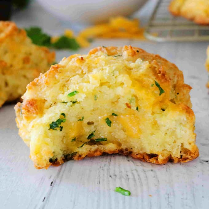 A biscuit with a bite taken out of it, and melty cheese and parsley speckled throughout the interior.