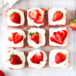 An overhead shot of strawberry brownies with cream cheese frosting.