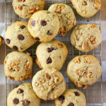 Walnut banana cookies and banana cookies with chocolate chips spread out on a cooling rack.