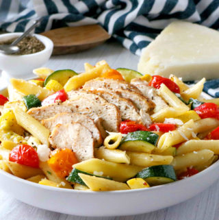 Sliced chicken sitting on top of pasta primavera in a bowl.