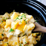 A wooden spoon full of cheesy crockpot potatoes being held over a slow cooker.