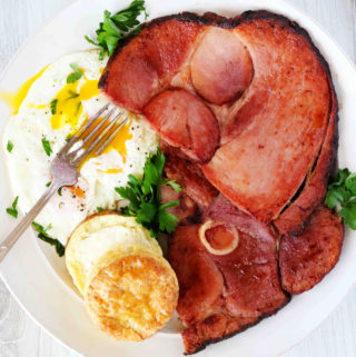 An overhead shot of ham steaks on a plate with an over-easy egg and a buttered biscuit.