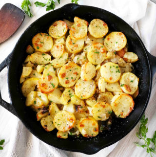 Potatoes Lyonnaise in a cast iron skillet with parsley scattered around.