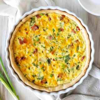 An overhead shot of Quiche Lorraine baked in a quiche dish with a scatter or green onions around it.
