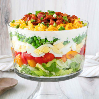 7-Layer Salad in trifle bowl with a serving spoon next to it and a towel laying behind the dish.