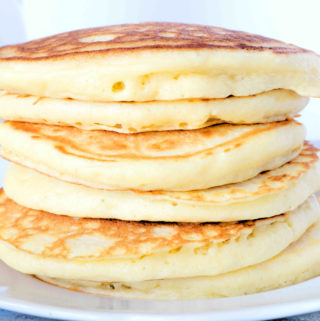 A stack of six fluffy pancakes on a plate.