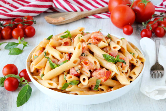 A bowl of penne pasta topped with pomodoro sauce and chopped tomatoes. There are tomatoes and basil leaves off to the side, as well as a napkin and fork.