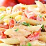 Penne pasta with a creamy tomato sauce dripping down the noodles.