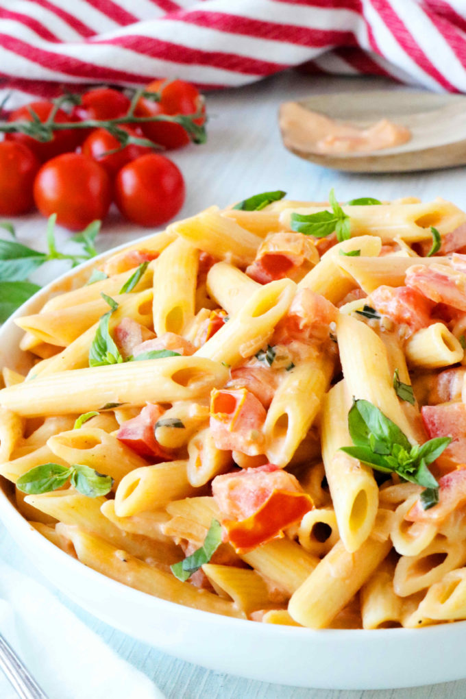 A bowl of penne pomodoro with penne pasta, chopped tomatoes, and a basil garnish.