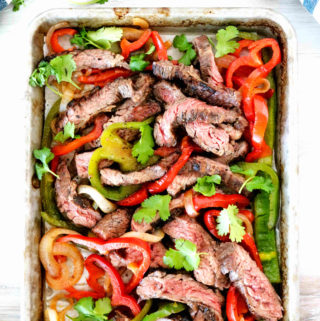 An overhead shot of beef mixed with white, red, and green fajita veggies.