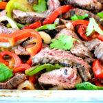 A sheet pan full of fajita veggies and sliced beef.