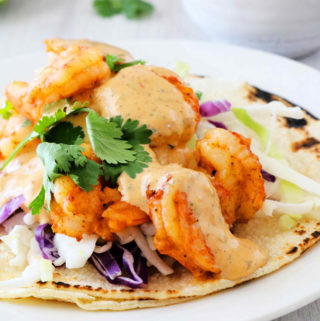 Shrimp piled high on a corn tortilla with chipotle sauce dripping down and cabbage on top.