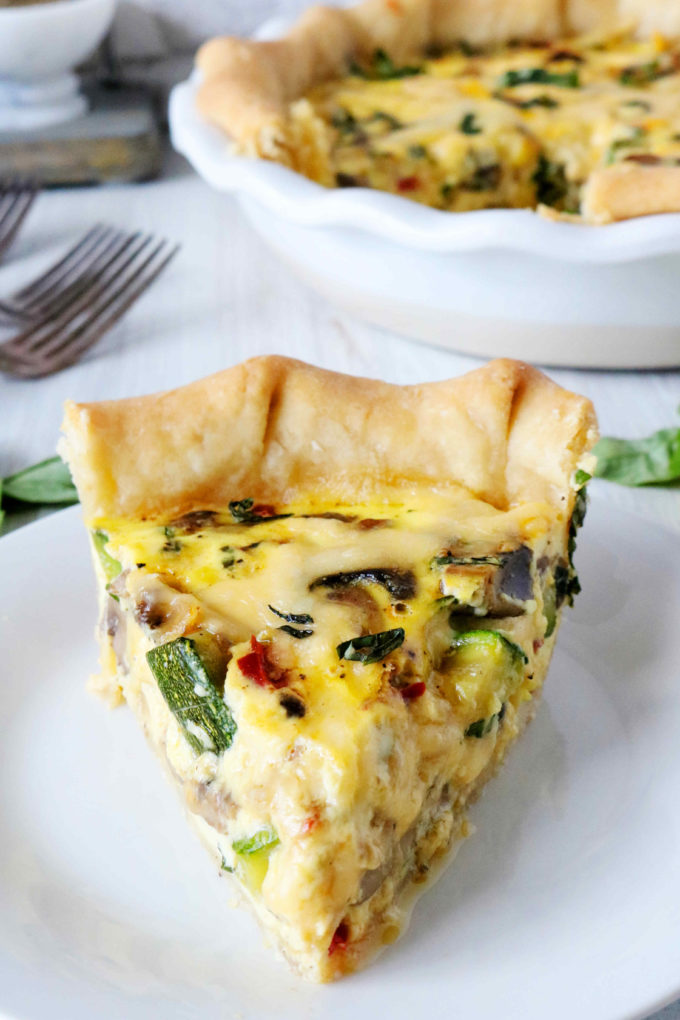 A slice of quiche with a pie dish in the background.